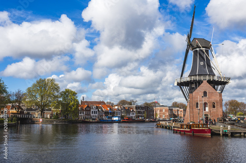 Fotobehang Praag View of Windmill De Adriaan reflected in the canal of the river Spaarne Haarlem North Holland The Netherlands Europe