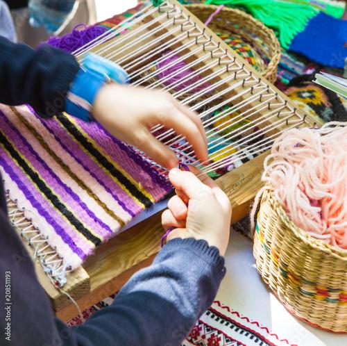 Hands of a girl weaving a Ukrainian mat made of multi-colored threads.