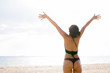 Young beautiful Asian tourist woman with arms raised at beach