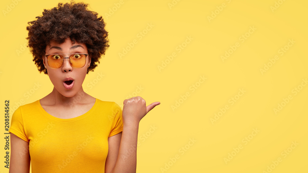 Fototapety, obrazy: Horizontal shot of beautiful female with dark skin keeps mouth opened, wears casual t shirt and yellow shades, indicates at blank space with thumb, has stupefied expression. People, ethnicity concept