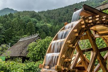 Točak mlina rotira se pod mlazom vode, pozadinom sela s tradicionalnim slamnatim krovovima