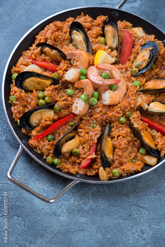 Paella with seafood in a serving pan, elevated view over blue stone surface, vertical shot