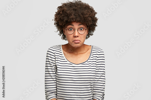 Fotografie, Obraz  Studio shot of puzzled beautiful African American female has hesitant and frustr