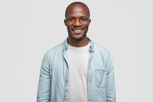 Horizontal Shot Of Happy Dark Skinned Male With Positive Smile On Face, Being In High Spirit As Achieves Success In Business Sphere, Dressed In Casual Outfit, Isolated Over White Background.