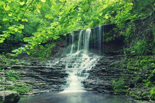 Keuken foto achterwand Watervallen Beautiful mountain rainforest waterfall with fast flowing water and rocks, long exposure. Natural seasonal travel outdoor background in hipster vintage style