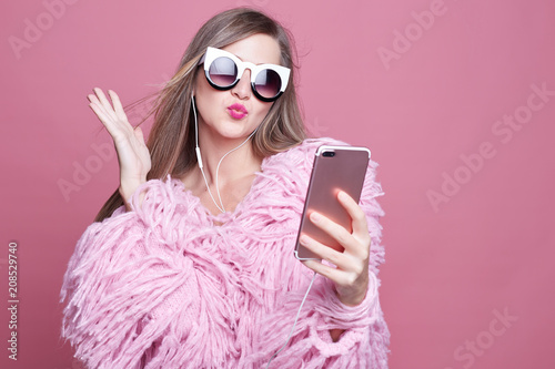 Photo Gorgeous lady dressed in funky bushy coat, wears make up, makes video call via smart phone and headphones, looking at gadget screen, taking selfie sending kiss to boyfriend, standing over pink wall