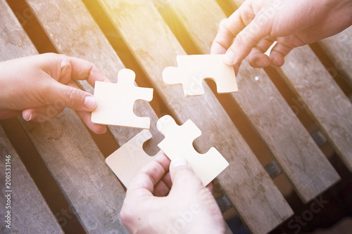 Business partnership or teamwork concept with a business people presenting a matching puzzle piece as they cooperate on finding an answer and solution, close up of their hands.