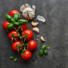 Food Background. Flat Lay Of Fresh Tomatoes With Basil, Garlic And Seasalt On Black Stone Background. Square Crop, Top View.