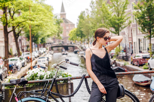 Photo  portrait of a beautiful fashionable young girl in the streets of Amsterdam, the