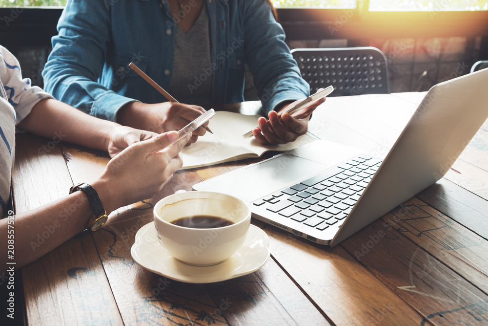 Fototapeta Coworkers young women of business teamwork working in cafe with laptop, mobile phone. meeting and brainstorming teamwork concept. New startup online marketing project. vintage film effect
