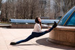 Beautiful athletic girl doing stretching in the city.
