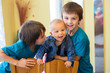 Two happy little preschool kids boys with baby boy brother in baby crib, playing together. Kids bonding