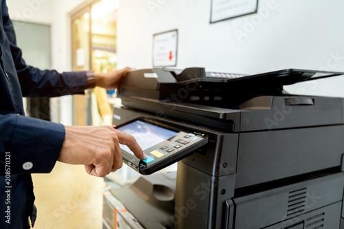 Bussiness man Hand press button on panel of printer, printer scanner laser office copy machine supplies start concept Canvas