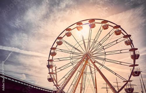 Poster Amusementspark Vintage toned picture of a Ferris wheel at sunrise.