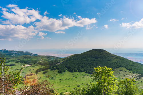 Foto op Plexiglas Blauwe hemel A beautiful landscape view over a mountain valley and forested mountain peaks of Velebit mountain range in Croatia of the Adriatic sea or coastline with islands. Summer in Croatia or travel concept
