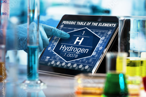 scientist consulting on the digital tablet data of the chemical element Hydrogen H / researcher working on the computer with the periodic table of elements