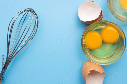 Raw fresh egg in glass bowl with eggshell and whisk on blue background top view Canvas Print