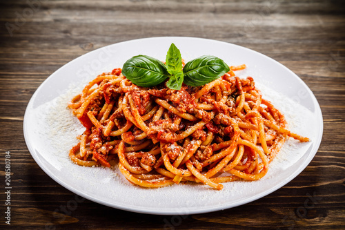 Fotografia Pasta with meat and tomato sauce on wooden table