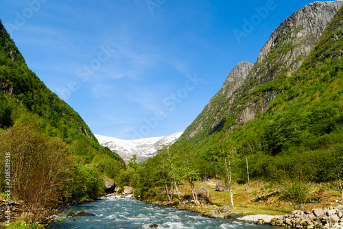 Fotobehang Gletsjers Valley landscape with a glacial meltwater river and a distant glacier. Location along the river Jordalselvi by the glacier Buarbreen.