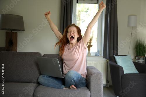 Photo Hübsche rothaarige Frau sitzt mit einem laptop auf ihrem Schoß auf einer Couch u