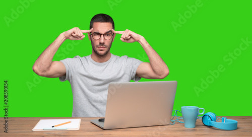 Fotografiet Concerned young man sitting at his desk with a gesture of concentration - Green