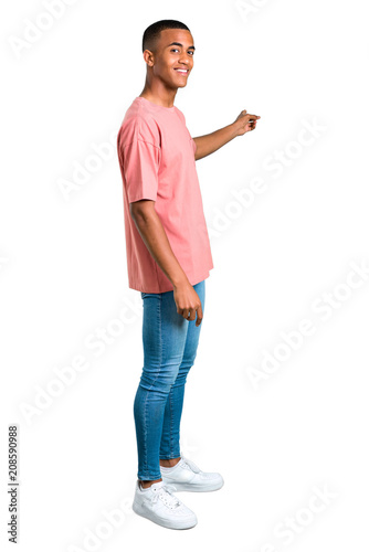 Photo  Standing young african american man pointing back with the index finger presenti