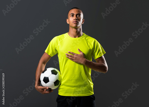 Photo Soccer player man with dark skinned playing catching a ball with his hands and s