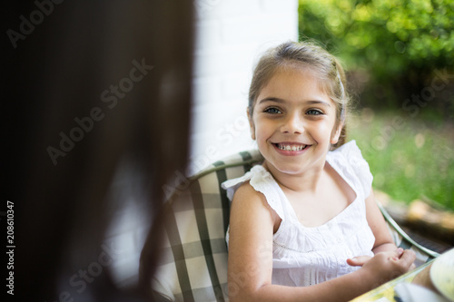 Crop view of cute girl sitting on chair in terrace and smiling on blurred green background