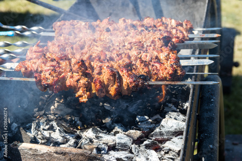 Foto op Plexiglas Grill / Barbecue Grilled kebab cooking on metal skewer. Roasted meat cooked at barbecue