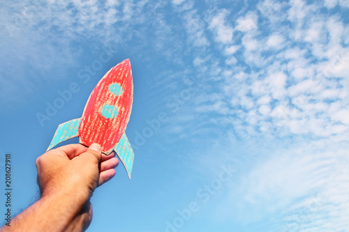Fototapeta  image of male hand holding a rocket against the sky