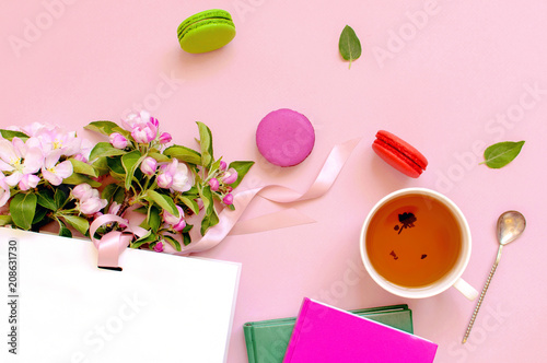 Fotografie, Obraz  Flat lay top view Cup of tea White gift bag with spring flowers and cake macaron