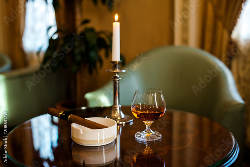 Fotografía  A glass of cognac, cigar and candles on a wooden table.