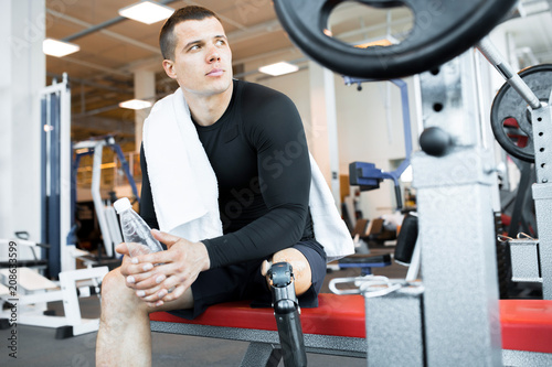 Young man sitting with amputated leg and drinking water in gym Wallpaper Mural