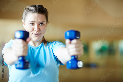 Fotografija Young female in blue t-shirt doing effective exercise with dumbbells while worki