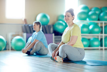 Young Chubby Cross-legged Woman And Her Groupmate In Activewear Sitting On Mats While Exercising In Fitness Center