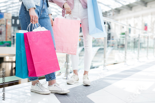 Fototapeta Close-up of unrecognizable hipster girls in sneakers and jeans holding bright shopping bags from concept stores while walking over mall obraz