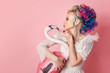 Stylish and beautiful woman with colored hair. Hugging a pink Flamingo figure.