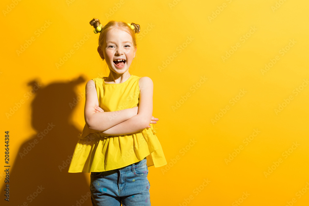 Fototapeta Girl with red hair on a yellow background. The beautiful girl laughs and folds her arms across her chest.