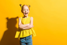 Girl With Red Hair On A Yellow Background. The Beautiful Girl Laughs And Folds Her Arms Across Her Chest.