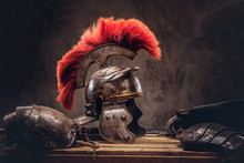 Complete Combat Equipment Of The Ancient Greek Warrior Lie On A Box Of Wooden Boards.