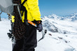 A mountaineer man holds an ice ax high in the mountains covered with snow. Close-up from behind. outdoor extreme outdoor climbing sports using mountaineering equipment