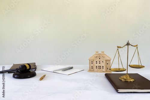 Gold brass balance scale with gavel and House model. housing and real estate law.