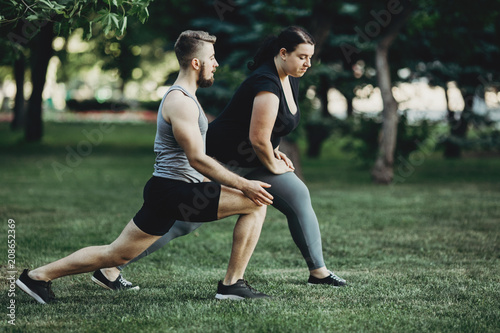 Overweight woman do lunges exercise with trainer Fototapet