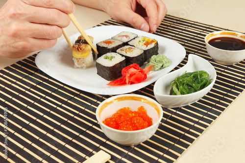 Male Hands Taking Sushi With Chopsticks Assorted Sushi