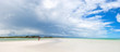 HOLBOX, MEXICO - MAY 22, 2018: Panaoramic view of tourists walking the beach at Holbox Island while a storm passes through