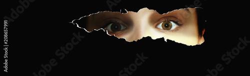 Fotografía  Neugierige junge Frau blickt durch einen Schlitz und schaut erschrocken bzw