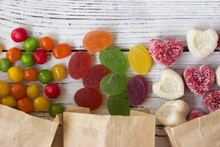 Sweets In Paper Bags. Multicolored Candy, Marmalade In The Form Of Heart On A White Wooden Background
