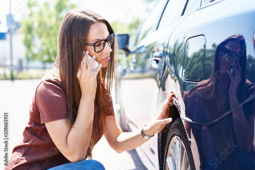 Fotografie, Obraz  Yougn woman inspecting her scratched car and calling insurance agent