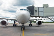 Commercial passenger airplane in the parking at the airport with a nose forward and a gangway - front view.