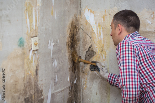 Valokuva  young man removing of mold and fungus from room wall with brush and antiseptic
